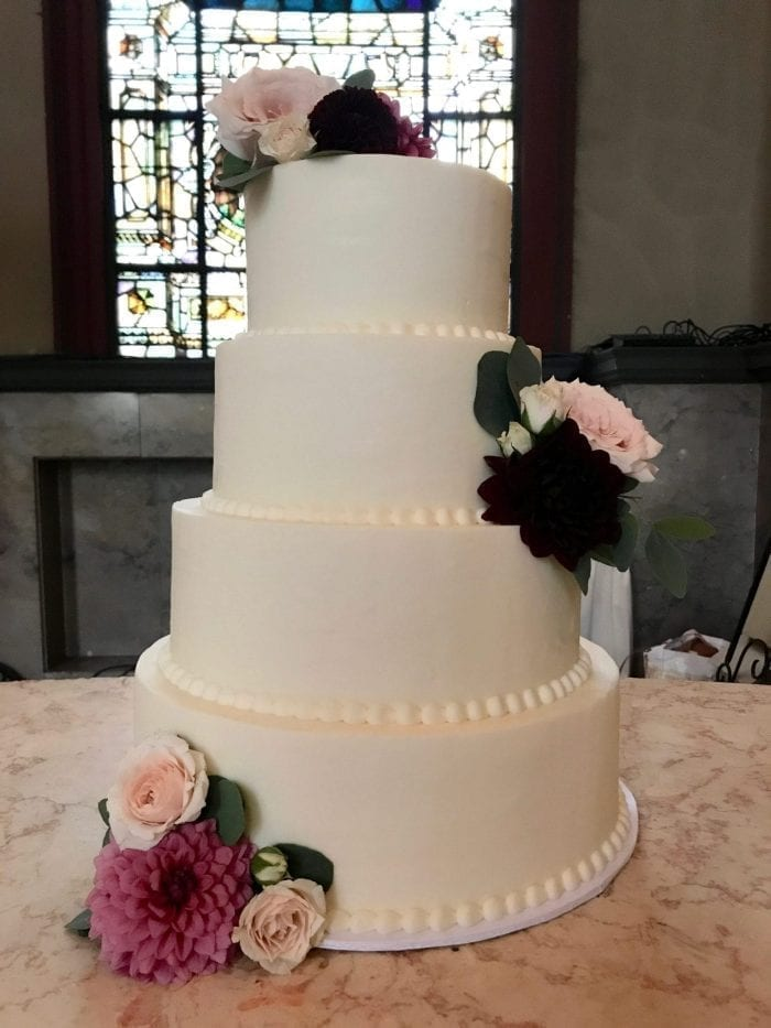 4 Tier Smooth Buttercream Wedding Cake with Fresh Flowers at Bell Event Center | 3 Sweet Girls Cakery