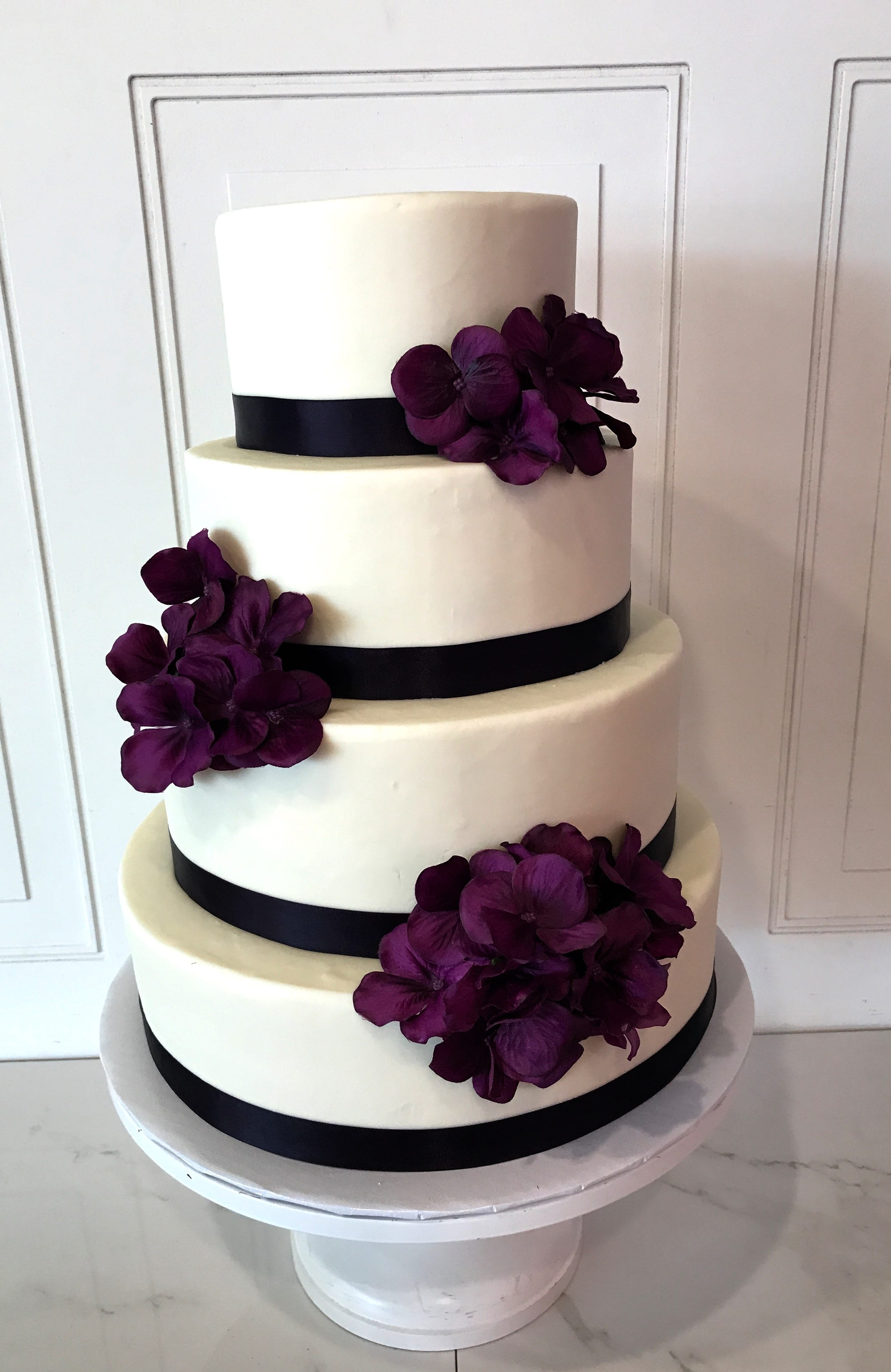 4 Tier White Wedding Cake with Black Bands and Purple Flowers | 3 Sweet Girls Cakery